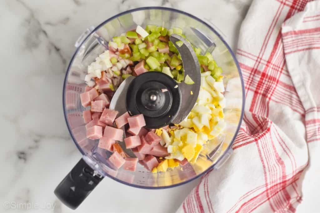 overhead view of a ninja food processor filled with ham, hard boiled eggs, celery, and onion to make ham salad