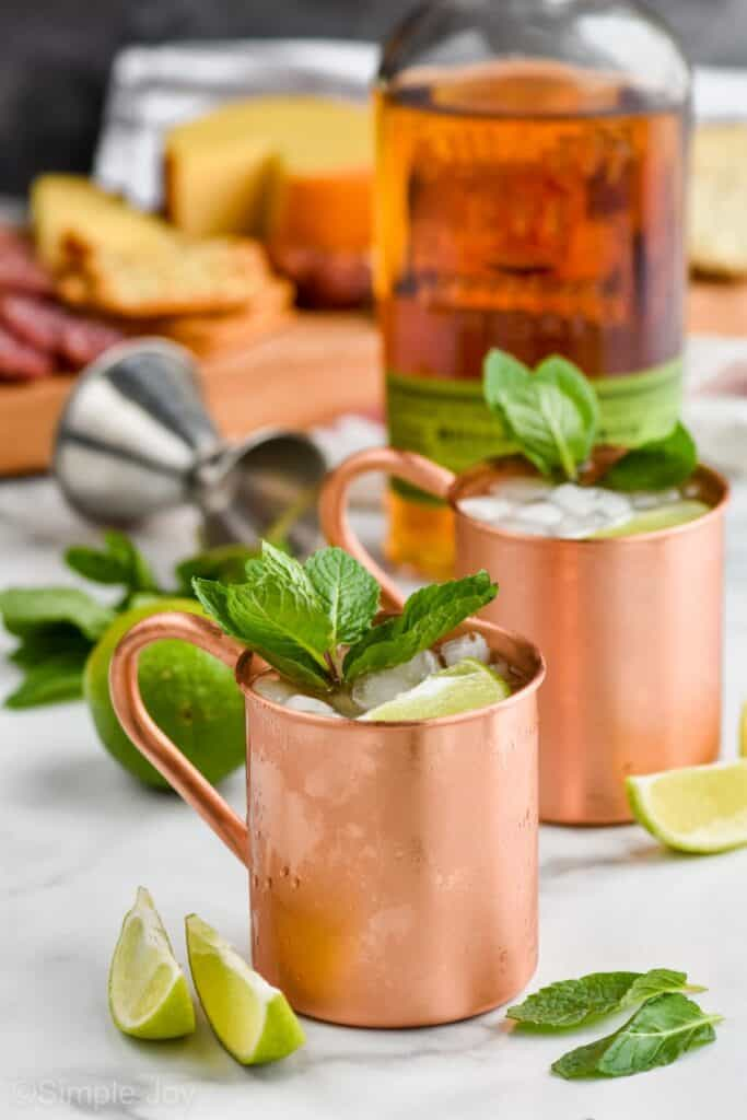 two copper mugs filled with ice, garnished with fresh mint with whiskey int he background and a metal jigger to make Irish mules