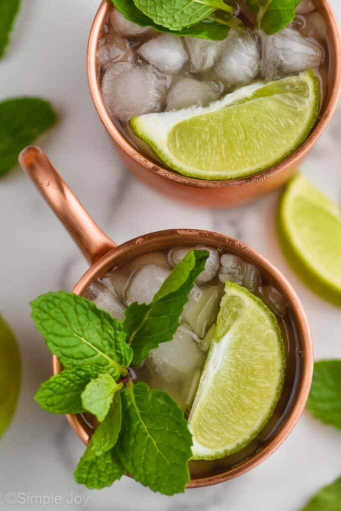 overhead view of two copper mugs filled with ice, garnished with lime wedges and fresh mint to make an Irish mule recipe