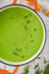 overhead view of a dutch oven with orange handles filled with pea soup garnished with fresh dill