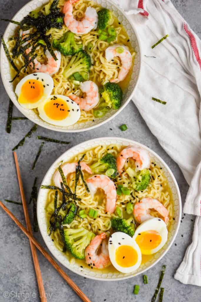 overhead view of two ramen bowls on a gray surface, each has shrimp, broccoli, and a soft boiled egg