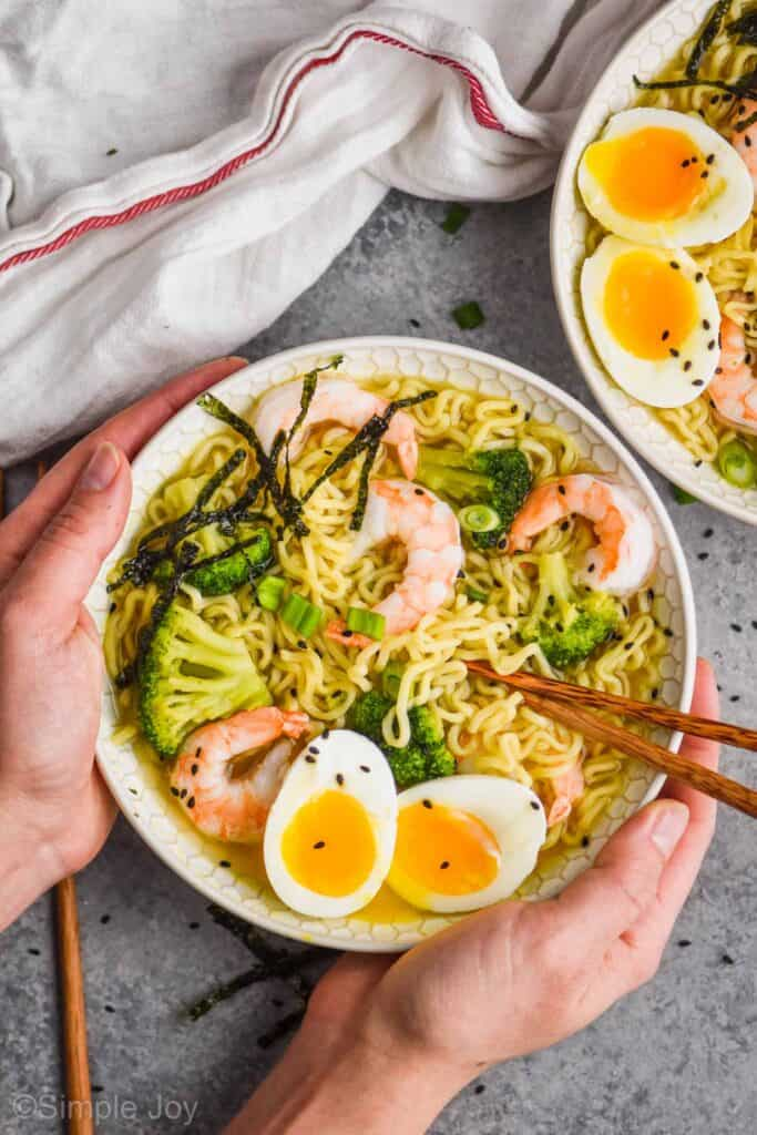 overhead view of two hands holding a bowl of easy ramen with a soft boiled egg, chopsticks, shrimp, and broccoli