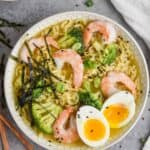 close up overhead view of a ramen recipe on a gray surface, bowl has small slices of seaweed over shrimp, broccoli, noodles, and soft boiled egg, all garnished with black sesame seeds