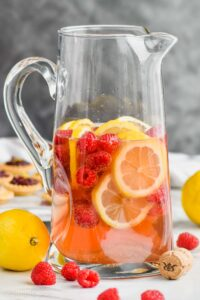 tall pitcher filled with sparkling rose sangria, fresh raspberries, and lemon slices