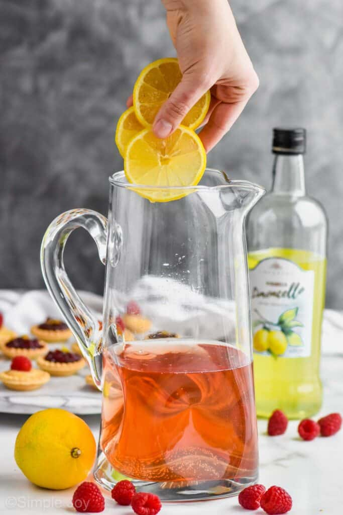 a hand dropping three lemon slices into a pitcher that has rose sangria in it