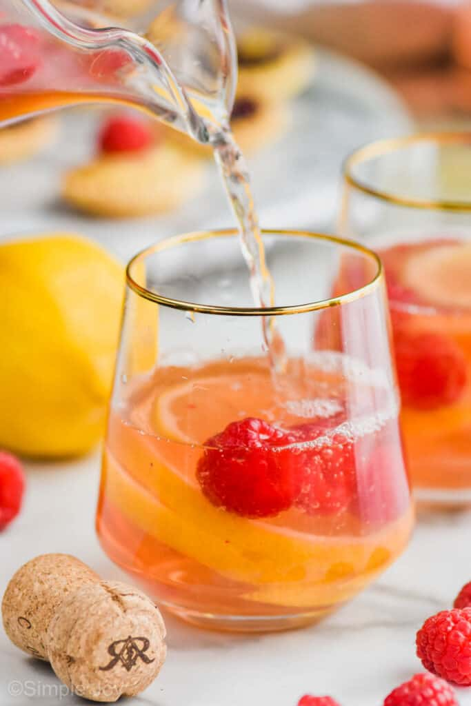 pouring Sparkling Rosé Sangria into a gold rimmed stemless wine glass with raspberries and lemons in it