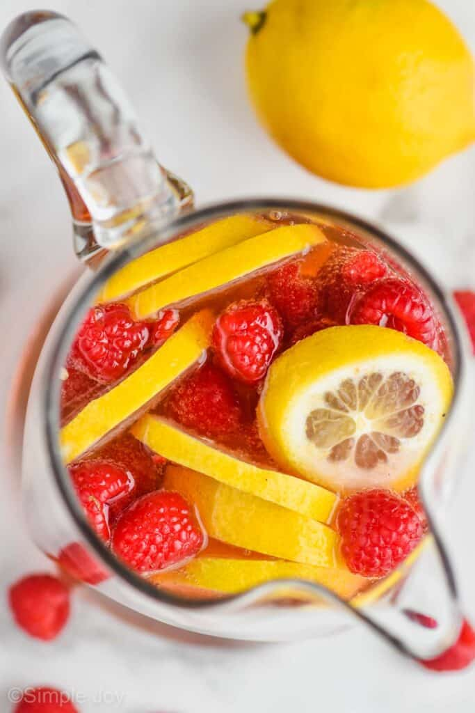 overhead view of a pitcher of rose sangria with fresh lemons and raspberries