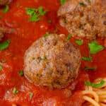 close up of Italian meatball on sauce and spaghetti