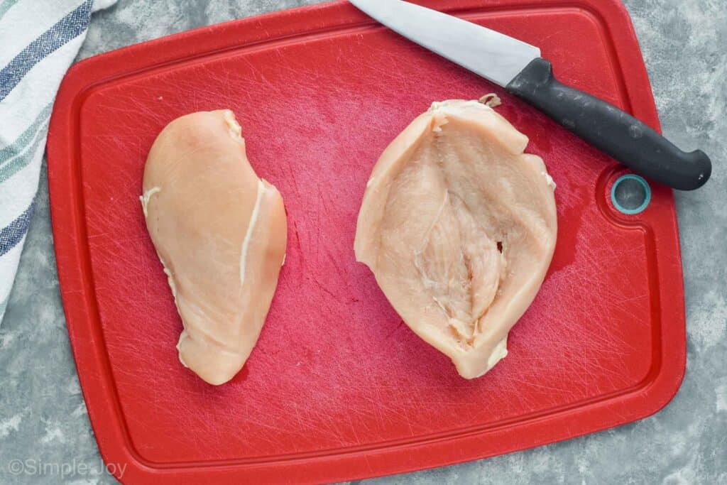 two raw chicken breasts on a red cutting board next to a knife with one being butterflied open
