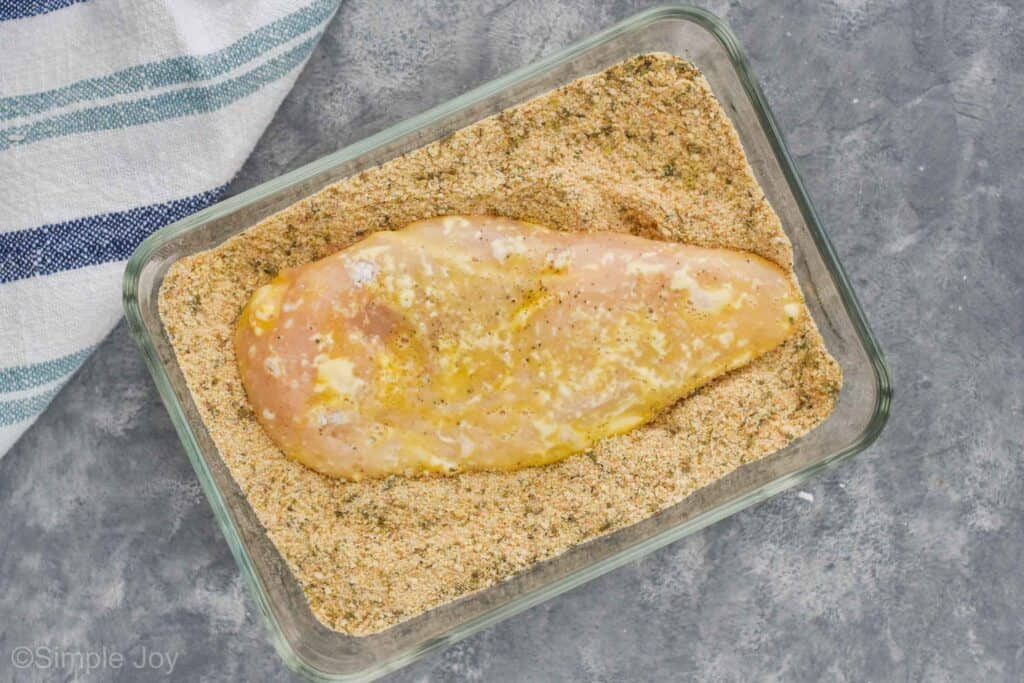a chicken breast that has been covered in egg in a rectangular baking dish in breadcrumbs
