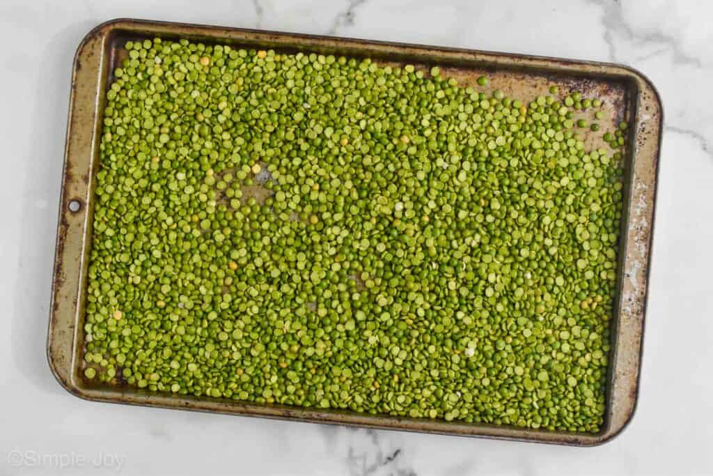 a galvanized baking sheet filled with dry split green peas on a white marble countertop