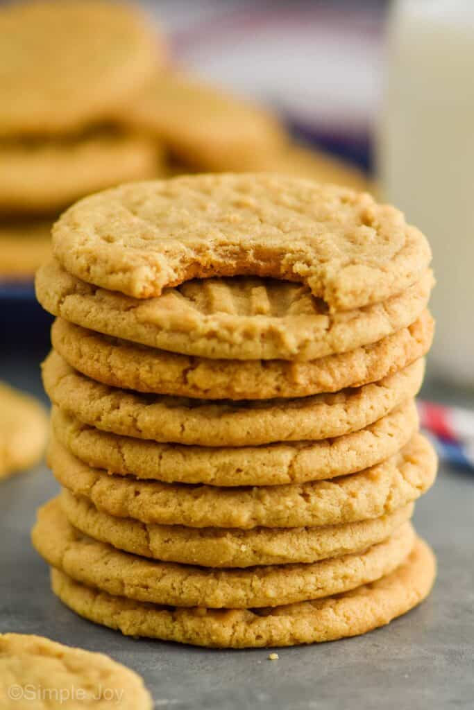 stack of 10 easy peanut butter cookies with the top one having a bite missing