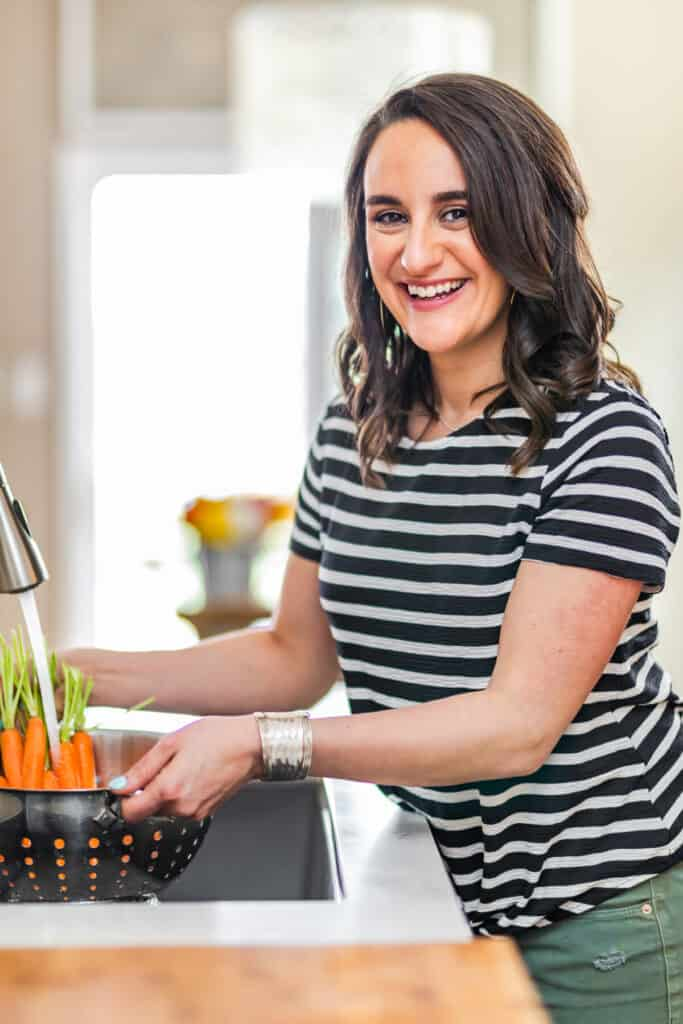 woman in a striped shirt washing carrots in a sink