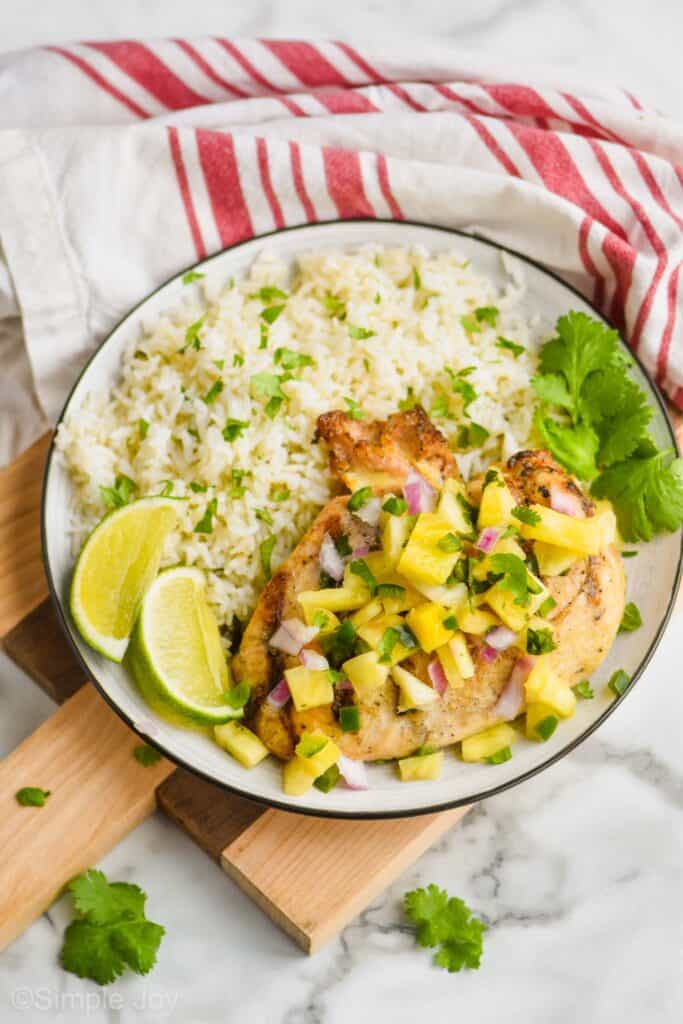 a grilled chicken breast covered in pineapple salsa on a plate with cilantro lime rice, lime wedges, and cilantro on a small cutting board with a striped cloth napkin
