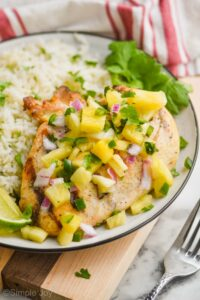 close up side view of the best marinated grilled chicken breast that is covered in pineapple salsa with fresh cilantro next to it on a plate