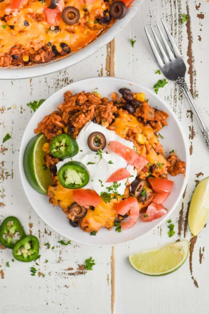overhead view of a white plate with taco bake casserole on it, garnished with jalapeño slices, olive slices, diced tomatoes, sour cream, and chopped cilantro