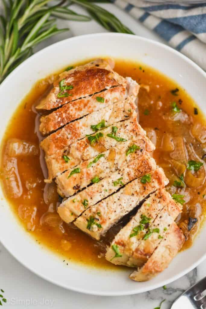 a chopped up boneless pork chop that has been pan fried, sliced, on a white plate with onion sauce around it, and covered with fresh parsley