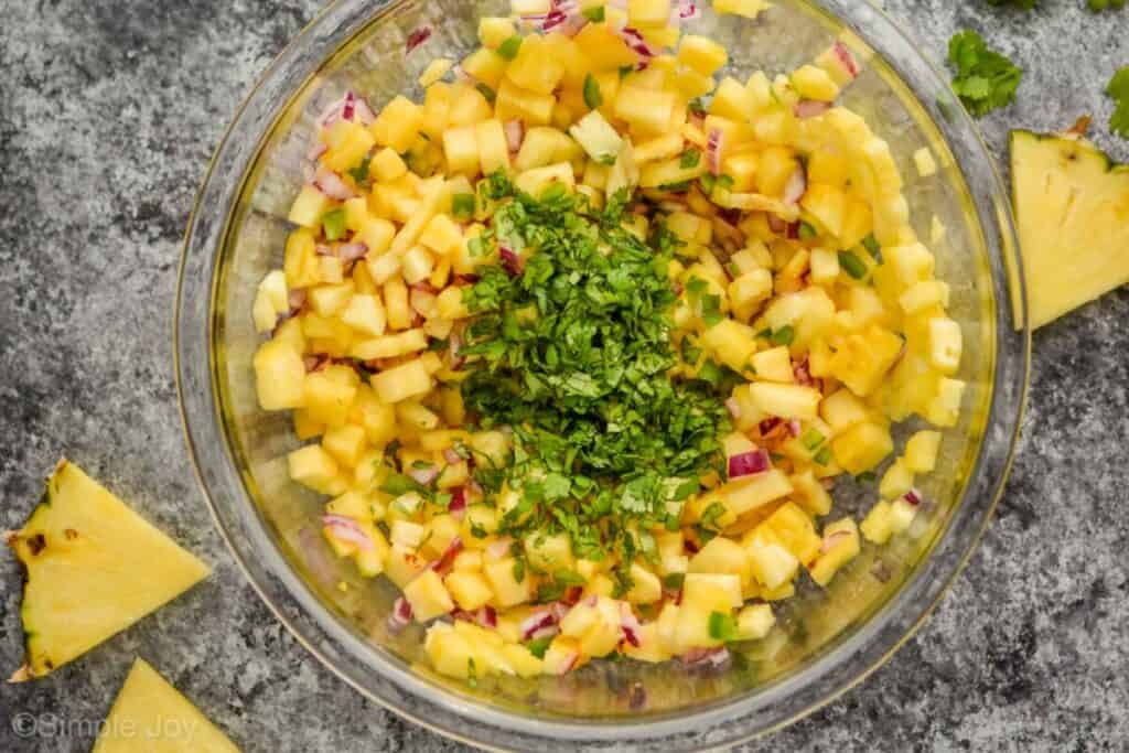 overhead view of pineapple salsa being mixed with a lot of fresh cilantro on top