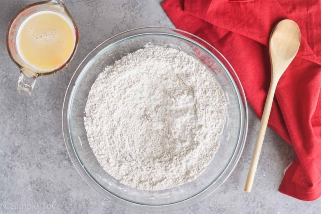overhead view of a bowl of flour with a wooden spoon next to it and a glass measuring cup filled with melted butter and warm milk