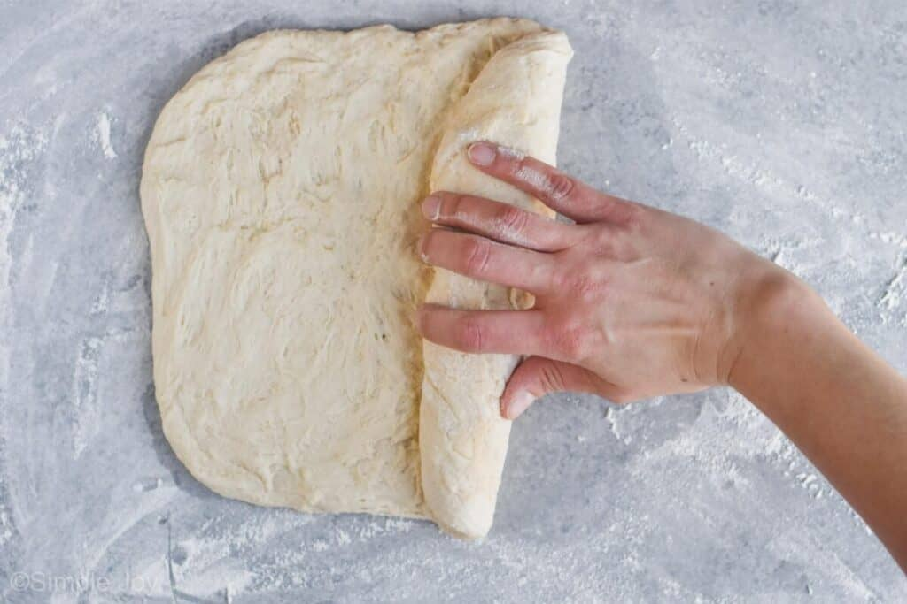 a hand rolling up dough for sandwich bread recipe