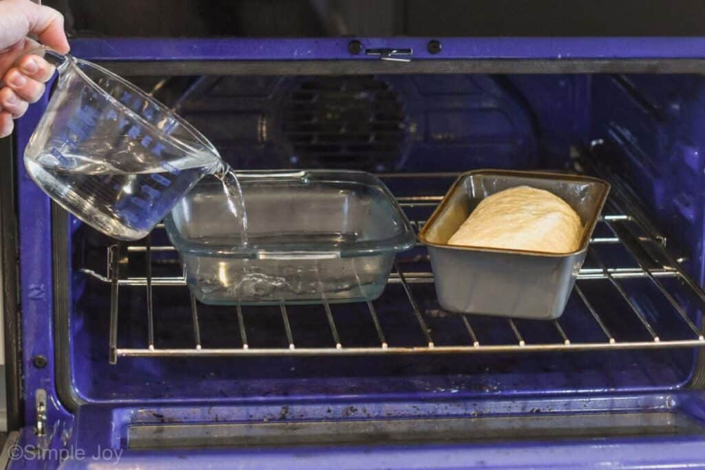 a loaf of sandwich bread dough in a bread pan in an oven with a hand pouring hot water into a square baking dish