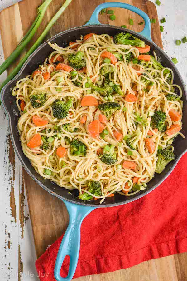 a cutting board with a teal skillet on it, inside is hummus pasta: spaghetti with sautéed carrots and broccoli that has a hummus based sauce