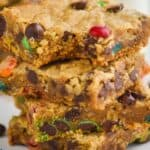 close up of four monster cookie bars with the a bite missing out of the top one