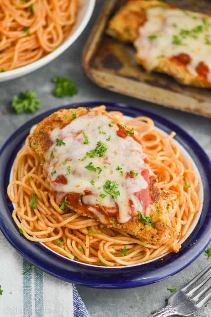 a piece of baked chicken parmesan that has been garnished with fresh parsley on a plate of spaghetti with a blue rim, with a tray of more chicken and a bowl of more spaghetti in the background