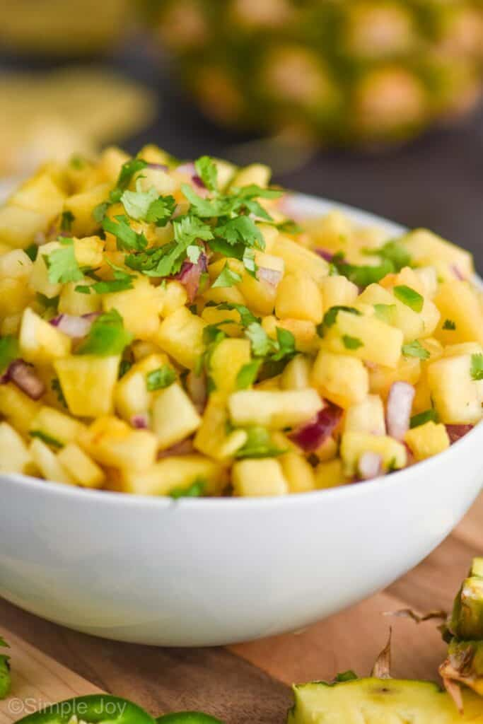 up close view of a white bowl full of pineapple salsa topped with chopped cilantro, with diced jalapeño and red onions