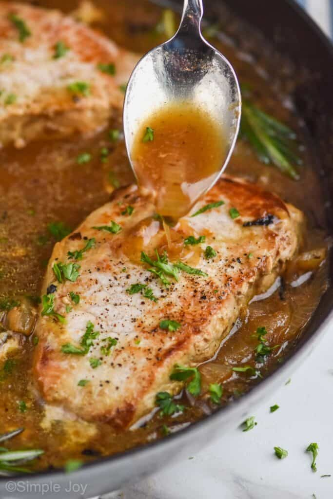 a spoon, spooning a brown sauce with onions onto a pan fried pork chop in a pan
