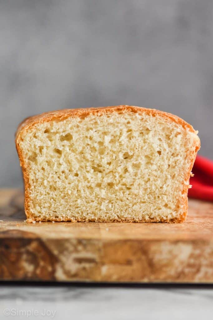 a straight on look at white bread sitting on a cutting board against a gray background