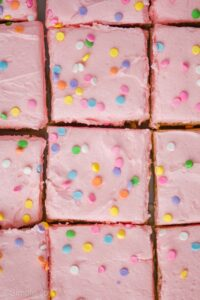 overhead view of sugar cookie bars that are cut and close together, frosting with pink frosting and pastel circle sprinkles