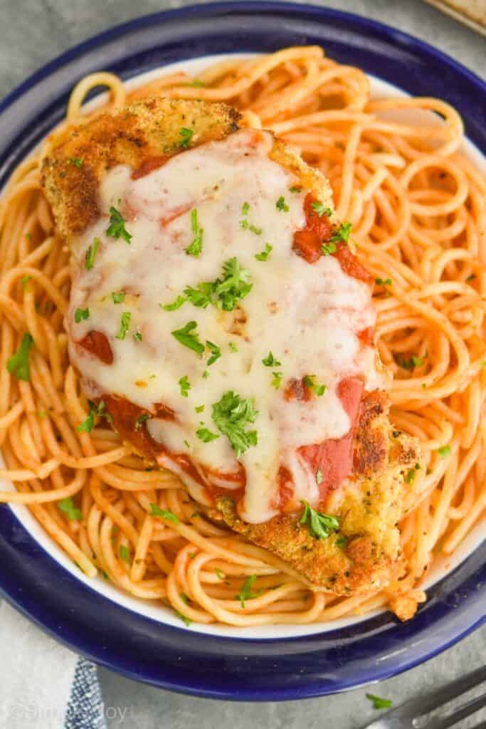 close up overhead view of a piece of baked parmesan chicken on a bed of spaghetti garnished with fresh parsley