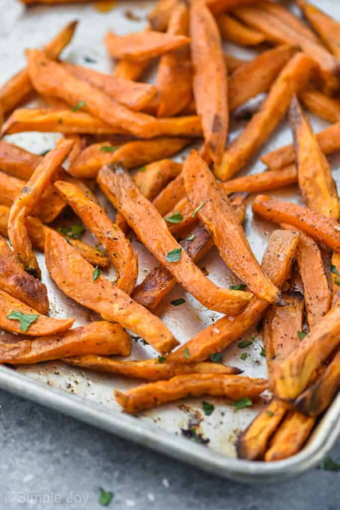 sweet potato fries on a baking sheet garnished with fresh parsley