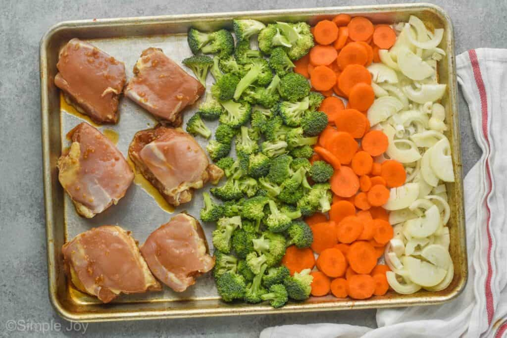 a sheet pan with chicken thighs, broccoli, carrots, and onions before being baked