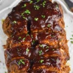 close up overhead view of a cooked meatloaf on a serving plate that has been slices, topped with more BBQ sauce, and garnished with parsley