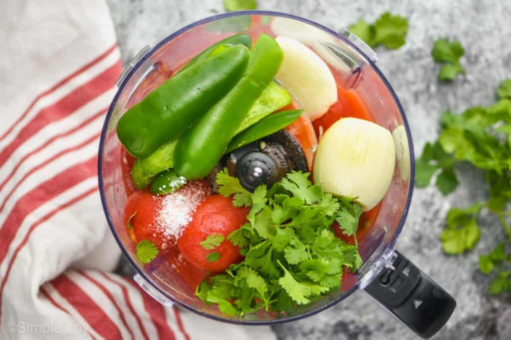 overhead view of a blender with unblended salsa ingredients: whole cilantro, a white onion cut in half, strips of jalapeño pepper sides, salt, and whole canned tomatoes