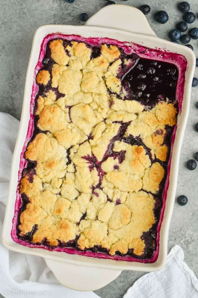 pulled back overhead view of ceramic dish full of blueberry cobbler recipe with one piece missing