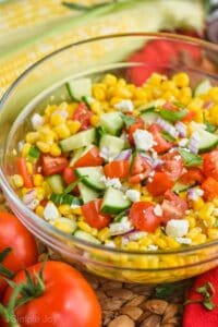 close up of corn salad in a glass bowl with fresh cut cucumbers, tomatoes, red onions, feta cheese, and fresh basil on top