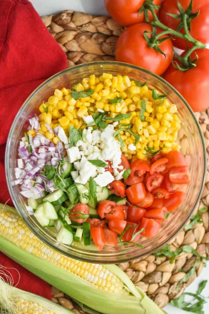 overhead view of a glass bowl full of the ingredients for corn salad recipe divided up