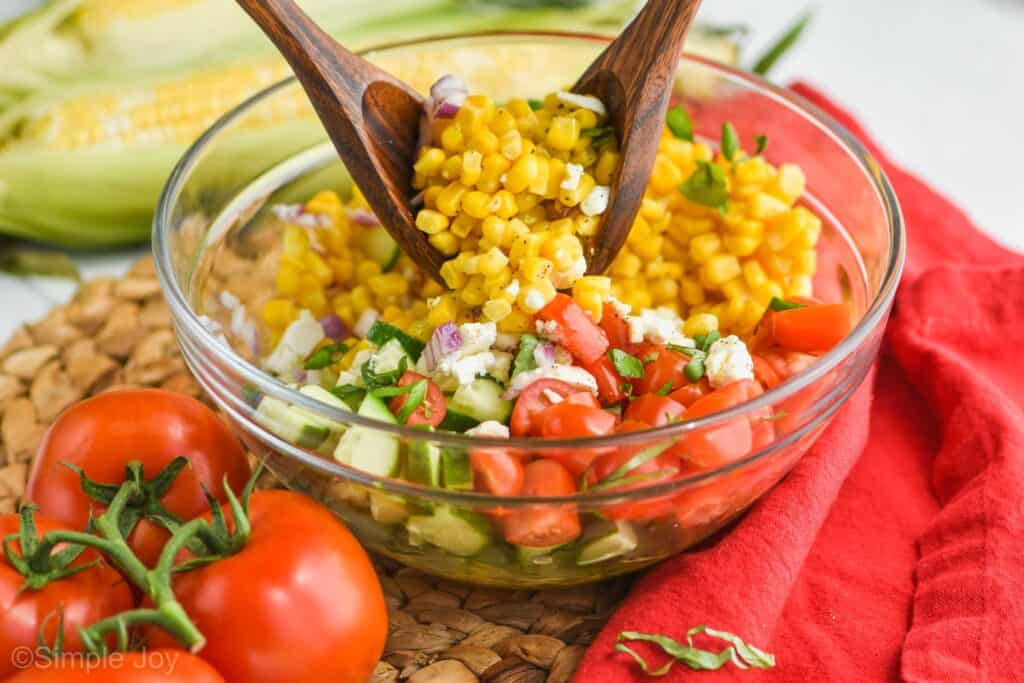 two wooden spoons tossing a glass bowl full of corn tomato salad
