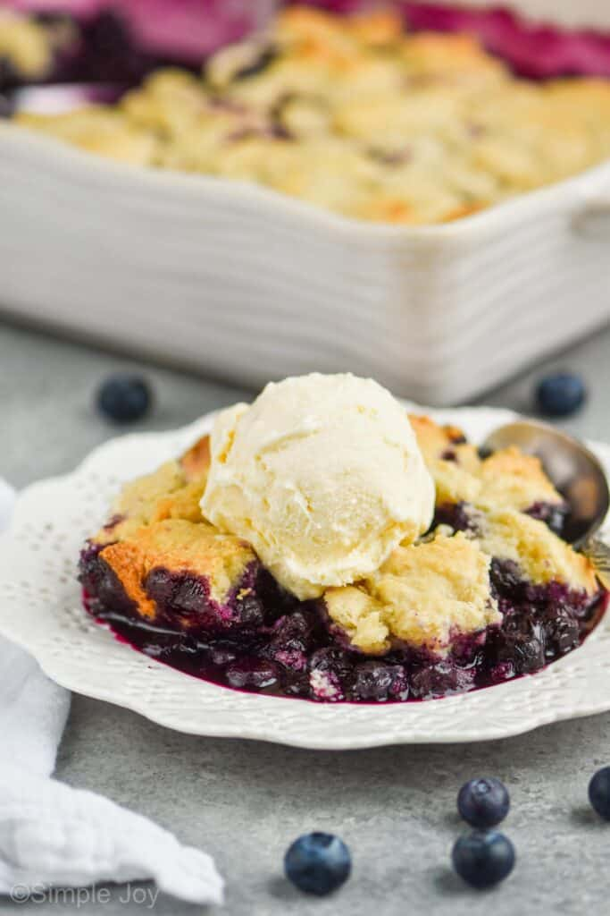 close up of a white dessert plate with blueberry cobbler recipe topped with vanilla ice cream, served with a spoon