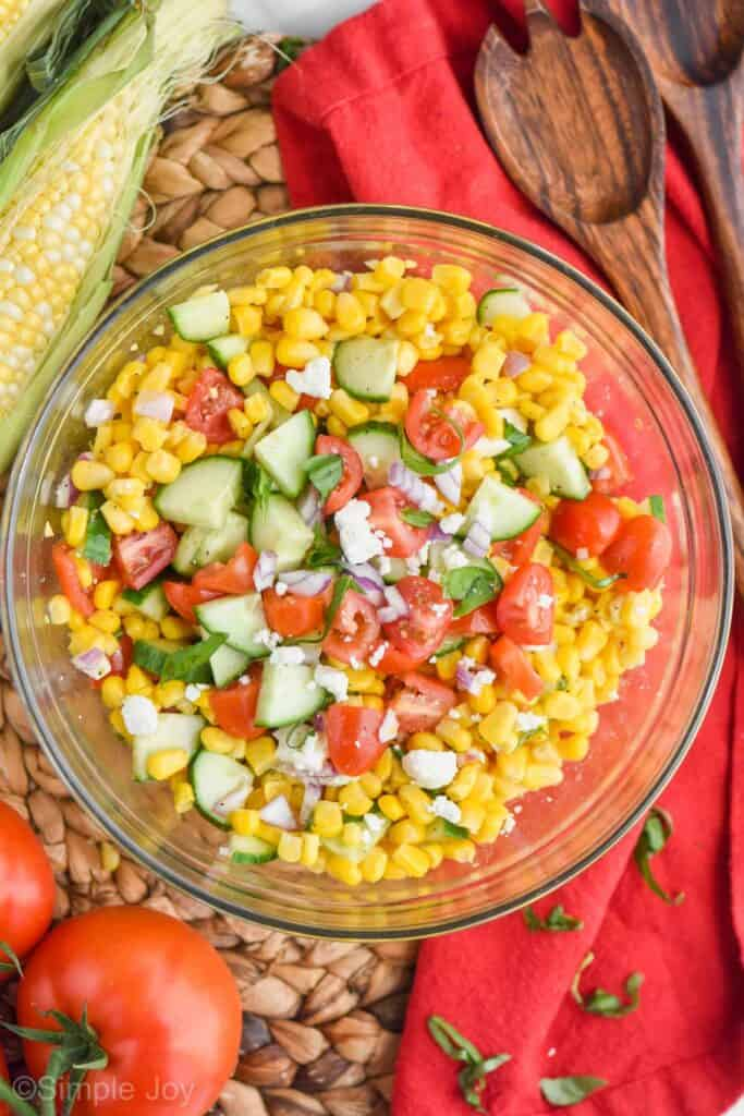 overhead of fresh corn salad in a glass bowl with fresh cut cucumber, tomato, red onion, feta and basil on top