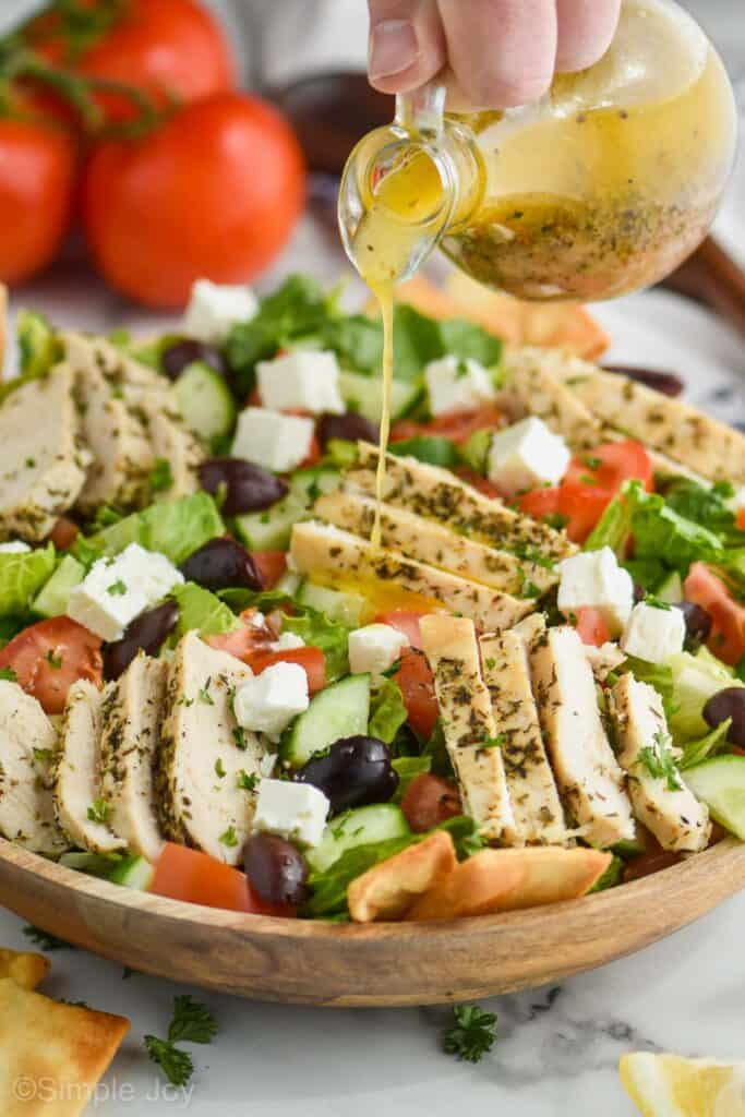 greek salad dressing being poured onto a greek salad with chicken