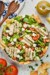 overhead view of a greek salad with chicken slices in a big serving bowl, garnished with fresh parsley, and pita chips off to the side