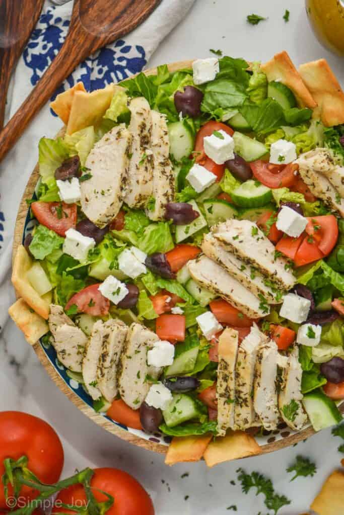 overhead view of a greek salad with chicken, with pita chips sticking out around the edges of the bowl and garnished with fresh parsley