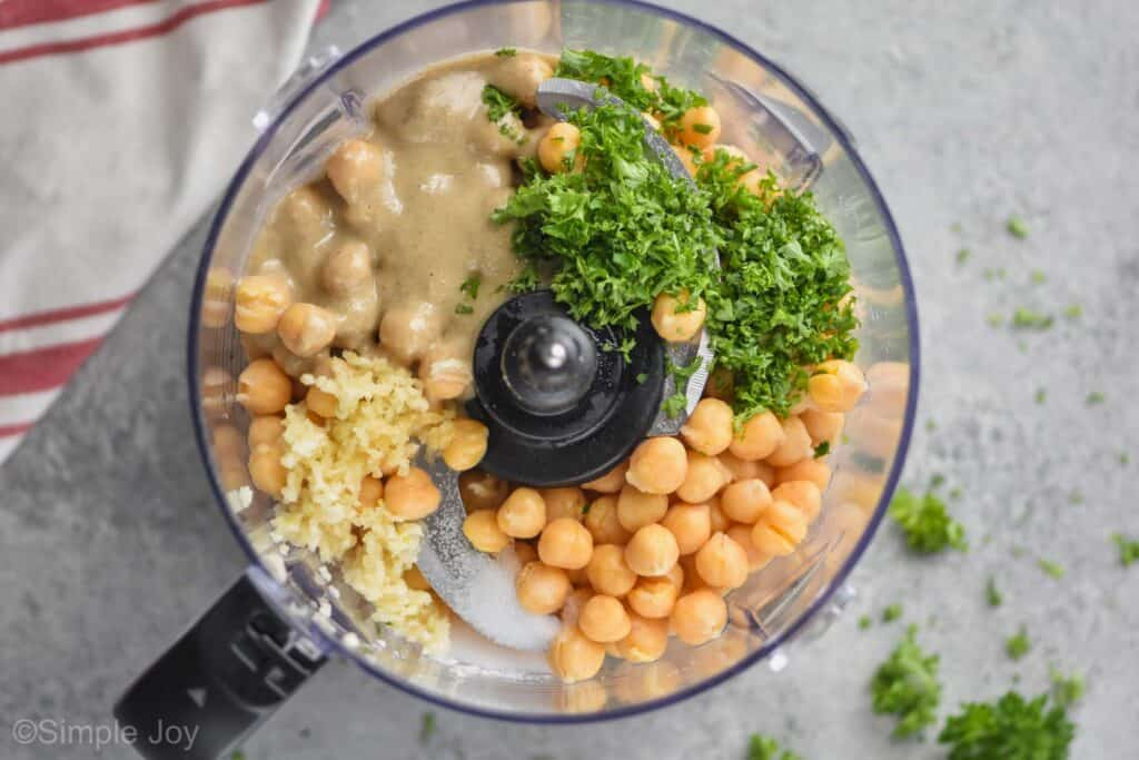 overhead view of a food processor with chickpeas fresh parsley minced garlic and tahini on a gray surface with spilled parsley and a cloth red and white napkin