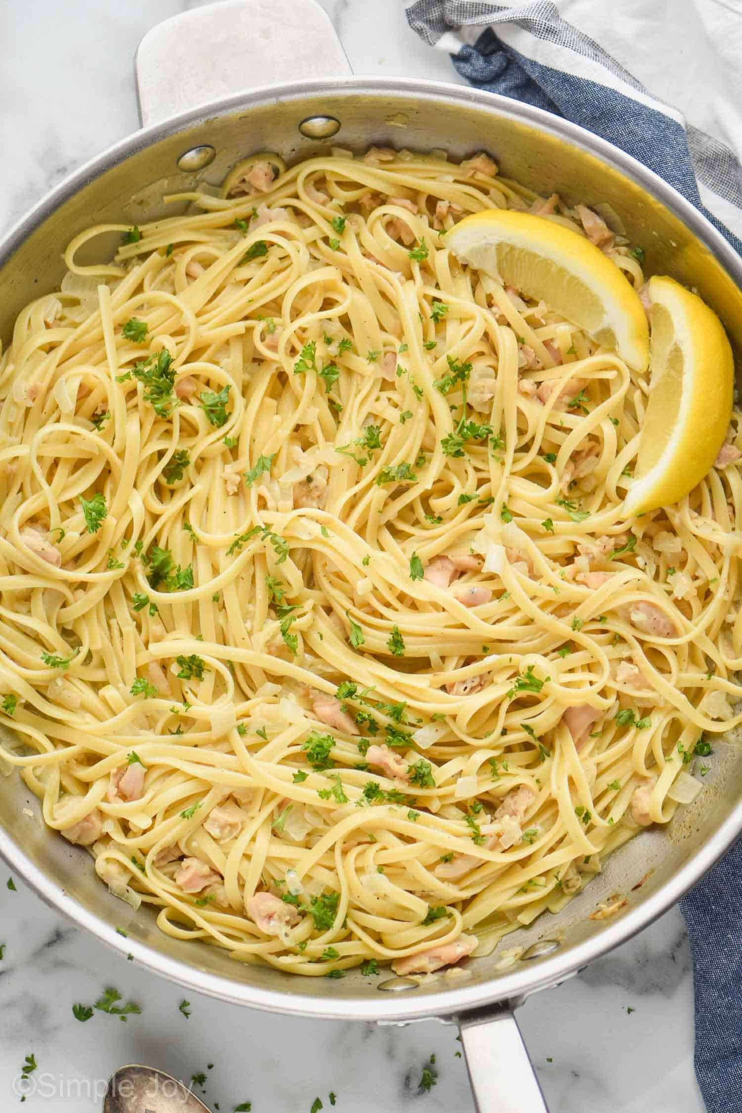 overhead photo of linguine with clams in a large skillet, garnished with fresh parsley and two lemon wedges