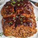 picture of a meatloaf on a serving plate, cut into with BBQ sauce on top and garnished with fresh parlsey