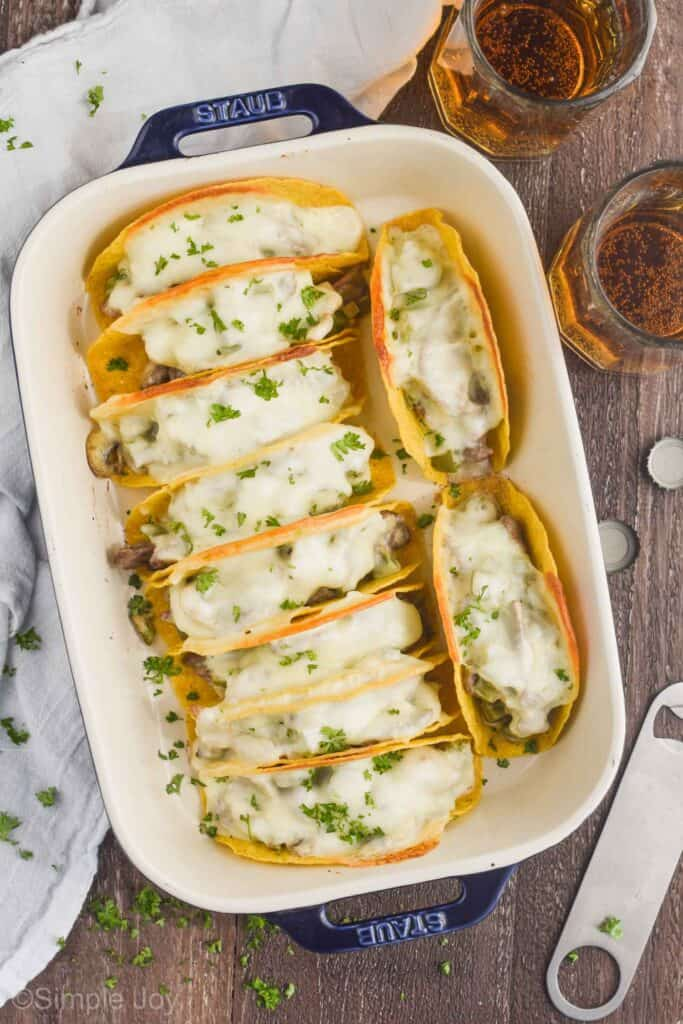 overhead view of a ceramic baking dish filled with 10 baked tacos that have white cheese melted on top, two beer mugs next to the casserole dish